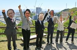 気候変動サミットに参加する政治家らにふんして石炭火力発電所建設反対を訴える人たち。奥は建設中の発電所=神奈川県横須賀市で2021年4月22日午前10時33分、丸山博撮影