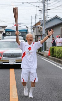 Takashi Miyata is seen during his leg in the Tokyo Olympic torch relay in Unzen, Nagasaki Prefecture, on May 7. 2021. (Pool photo)
