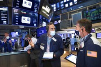 In this photo provided by the New York Stock Exchange, traders Gregory Rowe, center, and Robert Charmak, right, confer on the trading floor, on May 7, 2021. (Nicole Pereira/New York Stock Exchange via AP)