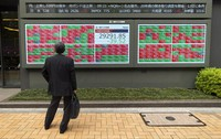 A man looks at an electric board showing Japan's Nikkei 225 index at a securities firm in Tokyo on May 7, 2021. (AP Photo/Hiro Komae)