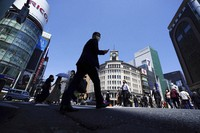 """People wearing protective masks to help curb the spread of the coronavirus walk through a crosswalk at the beginning of Japan's """"Golden Week"""" holidays on April 30, 2021, at Ginza shopping district in Tokyo. (AP Photo/Eugene Hoshiko)"""