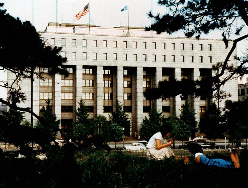 東京・有楽町にあったGHQ本部。屋上には星条旗がひるがえり、お堀端の石垣の上で女性がおしゃべりしている=1950年7月撮影