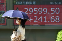 A woman wearing a protective mask walks in front of an electronic stock board showing Japan's Nikkei 225 index at a securities firm on May 10, 2021, in Tokyo. (AP Photo/Eugene Hoshiko)