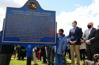 Maryland Gov. Larry Hogan, far right, Baltimore County Executive John Olszewski and Maryland House Speaker Adrienne Jones stand next to a new historic marker on May 8, 2021 in Towson, Md., that memorializes Howard Cooper, a 15-year-old who was dragged from a jailhouse and hanged from a tree by a mob of white men in 1885. (AP Photo/Brian Witte)