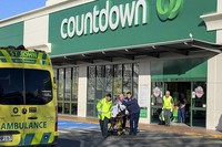 First responders take a victim to an ambulance outside a Countdown supermarket in central Dunedin, New Zealand, on May 10, 2021. (NZME via AP)