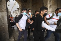 Palestinians evacuate a wounded protester during clashes with Israeli security forces at the Lions Gate in Jerusalem's Old City, on May 10, 2021. (AP Photo/Oded Balilty)