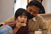 A student from Indonesia, right, helps a child eat a Korean pancake in Matsuyama, Ehime Prefecture, on April 7, 2021. (Mainichi/Ryo Endo)