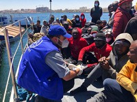 Aid workers for the International Organization for Migration provide assistance to migrants who were intercepted off the Libyan coast, at the Abu Sitta disembarkation point in Tripoli, on May 9, 2021. (International Organization for Migration via AP)