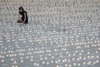 Woman lights a candle to commemorate victims of the COVD-19 pandemic at the Prague Castle in Prague, Czech Republic, on May 10, 2021. (AP Photo/Petr David Josek)
