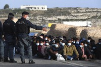 Migrants wearing face masks to curb the spread of COVID-19 sit at a pier as Italian police officers stand by, on the Sicilian island of Lampedusa, southern Italy, on May 10, 2021. (AP Photo/Salvatore Cavalli)