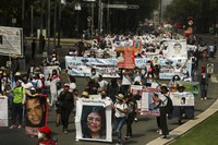 People carry photographs during a march in remembrance of those who have disappeared, on Mother's Day in Mexico City, on May 10, 2021. (AP Photo/Fernando Llano)