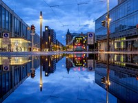 A tram is reflected in a puddle after the city is almost empty shortly after the end of the curfew in central Frankfurt, Germany, on May 11, 2021. (AP Photo/Michael Probst)
