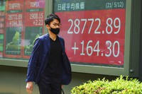 A man wearing a protective mask walks in front of an electronic stock board showing Japan's Nikkei 225 index at a securities firm on May 12, 2021, in Tokyo. (AP Photo/Eugene Hoshiko)