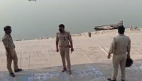 This frame grab from video provided by KK Productions shows police officials stand guard at the banks of the river where several bodies were found lying in Ghazipur district, Uttar Pradesh state in India, on May 11, 2021. (KK PRODUCTIONS via AP)