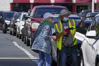 A customer helps pumping gas at Costco, as other wait in line, on May 11, 2021, in Charlotte, North Carolina. (AP Photo/Chris Carlson)