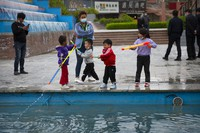 Children play with water toys at a public square in Aksu in western China's Xinjiang Uyghur Autonomous Region, on April 20, 2021. (AP Photo/Mark Schiefelbein)
