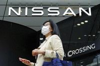 A woman wearing a face mask to to help curb the spread of the coronavirus walks by the logo of Nissan seen at the automaker's showroom in Tokyo on May 11, 2021. (AP Photo/Eugene Hoshiko)