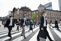 People wearing face masks walk in front of JR Tokyo Station on May 12, 2021, under a coronavirus state of emergency that was extended in the capital the same day amid a resurgence in infections. (Kyodo)