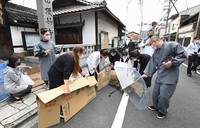Ducklings are seen being guided by locals with sections of cardboard as they move to the Kamo River in Kyoto's Sakyo Ward on May 13, 2021. (Mainichi/Kazuki Yamazaki)