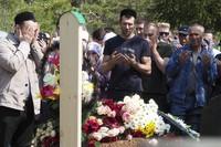 People pray next to the grave of Elvira Ignatieva, an English language teacher who was killed at a school shooting, in Kazan, Russia, on May 12, 2021. (AP Photo/Dmitri Lovetsky)