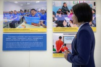 A tour guide stands near a display showing images of people at locations described as vocational training centers in southern Xinjiang at the Exhibition of the Fight Against Terrorism and Extremism in Urumqi in western China's Xinjiang Uyghur Autonomous Region, on April 21, 2021. (AP Photo/Mark Schiefelbein)