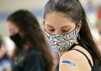 In this Thursday, April 8, 2021, file photo, Kent State University student Regan Raeth, of Hudson, Ohio, looks at her vaccination bandage as she waits for 15 minutes after her shot in Kent, Ohio. (AP Photo/Phil Long)