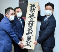 Minister for Promoting Dynamic Engagement of All Citizens Tetsushi Sakamoto, center, is seen holding a sign for the office of the minister for loneliness, in Tokyo's Chiyoda Ward on Feb. 19, 2021. (Pool photo)