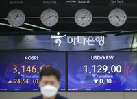An employee of a bank walks by screens showing the Korea Composite Stock Price Index (KOSPI), left, and the foreign exchange rate between U.S. dollar and South Korean won at the foreign exchange dealing room in Seoul, South Korea, on May 14, 2021. (AP Photo/Lee Jin-man)