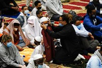 A worshipper helps a child with a mask before he and others perform an Eid al-Fitr prayer at the Masjidullah Mosque in Philadelphia, on May 13, 2021. (AP Photo/Matt Rourke)