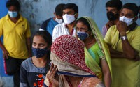 In this April 19, 2021, file photo, people wearing masks as a precaution against the coronavirus wait to test for COVID-19 at a hospital in Hyderabad, India. (AP Photo/Mahesh Kumar A)