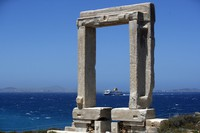 A ferry approaches the port where Portara, a marble gate which is part of an unfinished temple of Apollo of 530 B.C, stands atop a hill on the Aegean island of Naxos, Greece, on May 11, 2021. (AP Photo/Thanassis Stavrakis)