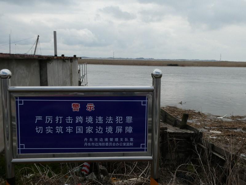 「国境をまたぐ犯罪は厳重に取り締まる」と書かれた看板の向こう側に、かつて密輸の現場だった鴨緑江が見える=中国・丹東市内で2021年5月、米村耕一撮影