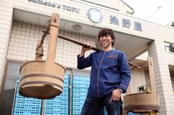 かつて豆腐の販売で使われていたおけを肩に乗せ、ポーズをとる染野屋の小野篤人社長=茨城県取手市で、小川昌宏撮影