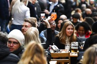 In this Monday, April 12, 2021 file photo, a woman takes a photo on her phone of her drink in Soho, London, as some of England's coronavirus lockdown restrictions were eased by the government. (AP Photo/Alberto Pezzali)