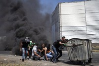 Palestinian demonstrators take cover during clashes with Israeli forces at the Hawara checkpoint, south of the West Bank city of Nablus, on May 14, 2021. (AP Photo/Majdi Mohammed)