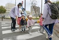 Nursery teachers walk with children in the city of Osaka on Feb. 14, 2020. (Kyodo)