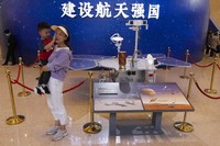 Visitors to an exhibition on China's space program pose for photos next to a life size model of the Chinese Mars rover Zhurong, named after the Chinese god of fire, at the National Museum in Beijing on May 6, 2021. (AP Photo/Ng Han Guan)