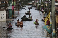 Residents navigate a flooded street in Anama, Amazonas state, Brazil, on May 13, 2021. (AP Photo/Edmar Barros)
