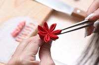 Folded pieces of silk are being attached to a circle-shaped construction paper base, as part of the process of creating