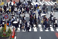 People wearing protective masks to help curb the spread of the coronavirus walk along a pedestrian crossing on May 14, 2021, in Tokyo. (AP Photo/Eugene Hoshiko)