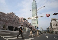 People wear face masks walk past Taipei 101 building after the COVID-19 alert raise to level 3 in Taipei, Taiwan, on May 15, 2021. (AP Photo/Chiang Ying-ying)