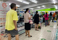 People wear masks and observe social distancing while lining up to pay at a supermarket in Singapore, on May 14, 2021. (AP Photo/Zen Soo)