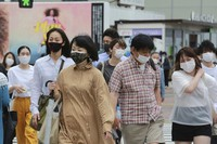 People wearing face masks to protect against the spread of the coronavirus walk on a street in Tokyo, on May 18, 2021. (AP Photo/Koji Sasahara)