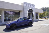 In this April 2, 2021 file photo two women in an electric car drive into a Tesla delivery location and service center in Corte Madera, Calif. (AP Photo/Eric Risberg)