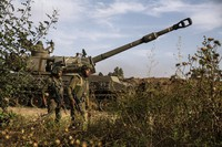 Two Israeli soldiers walk around an artillery unit, at the Israeli Gaza border, on May 16, 2021. (AP Photo/Heidi Levine)