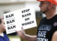 In this May 21, 2019, file photo, an abortion rights advocate hoists a sign at the Capitol in Jackson, Miss., as they rally to voice their opposition to state legislatures passing abortion bans. (AP Photo/Rogelio V. Solis)