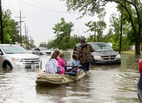 Parents use boats to pick up students from schools after nearly a foot of rain fell in Lake Charles, La., on May 17, 2021. (Rick Hickman/American Press via AP)