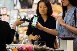 タイはキャッシュレスの導入が早かった。(2017年9月、バンコクの食料品店でスマートフォンからQRコードをスキャンする人)Bloomberg