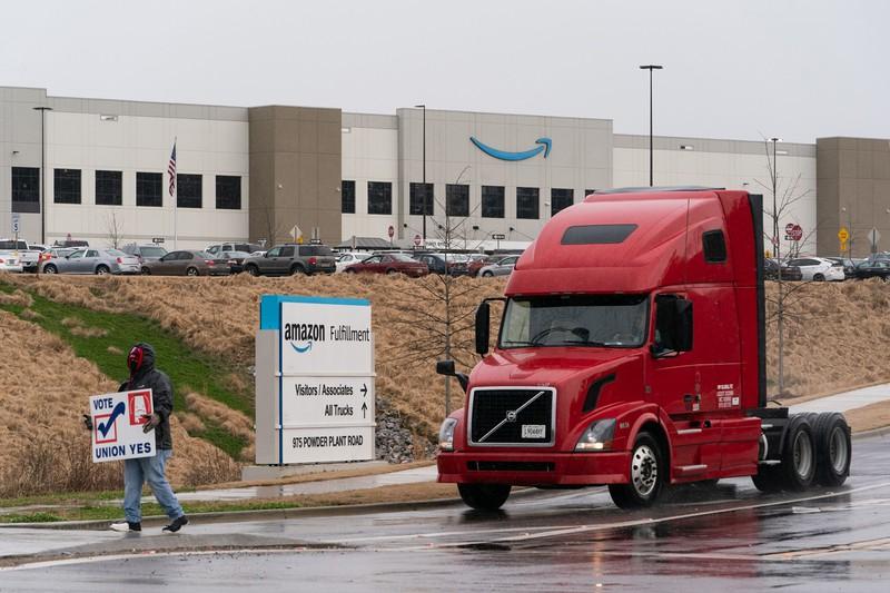 アマゾンの巨大倉庫の前で「組合賛成」のプラカードを掲げる従業員(米アラバマ州) (Bloomberg)