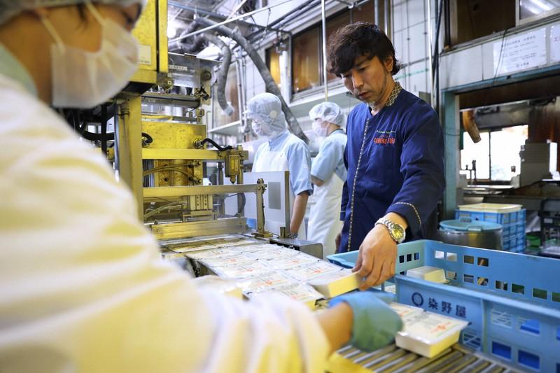 本店の工場を見て回る染野屋の小野篤人社長(右)=茨城県取手市で、小川昌宏撮影